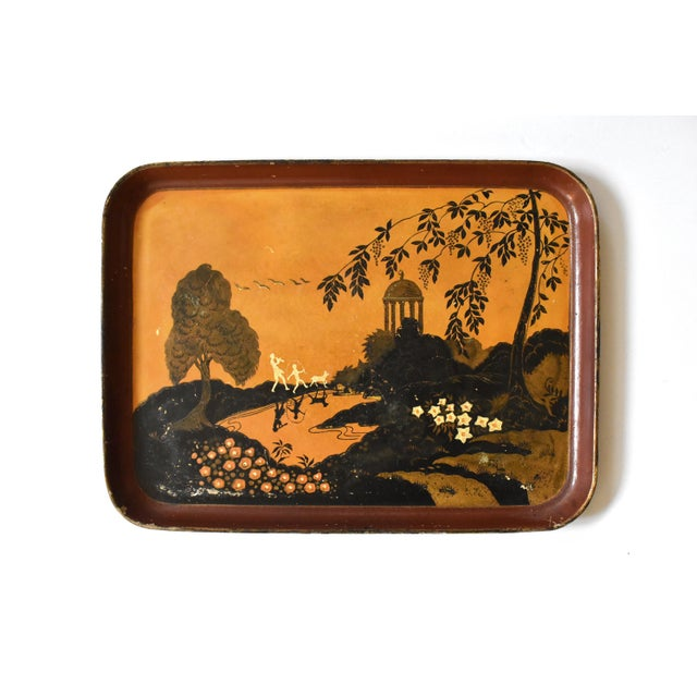 An antique, Art Deco, c. 1920s tray in orange, gold, black, and cream, with a landscape with flowers, trees, a classical...