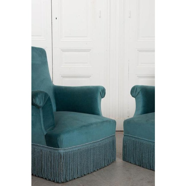 This delightful three-piece parlor suite, composed of two armchairs and a settee, is upholstered in a worn cerulean velvet...