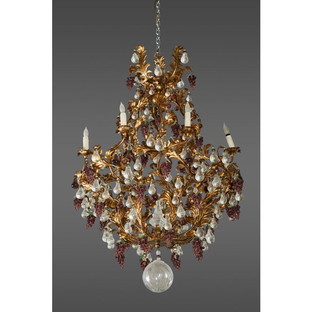 A stunning and dramatic Parisian chandelier. It's elaborate multi-branch acanthus themed gilt iron armature profusely hung...