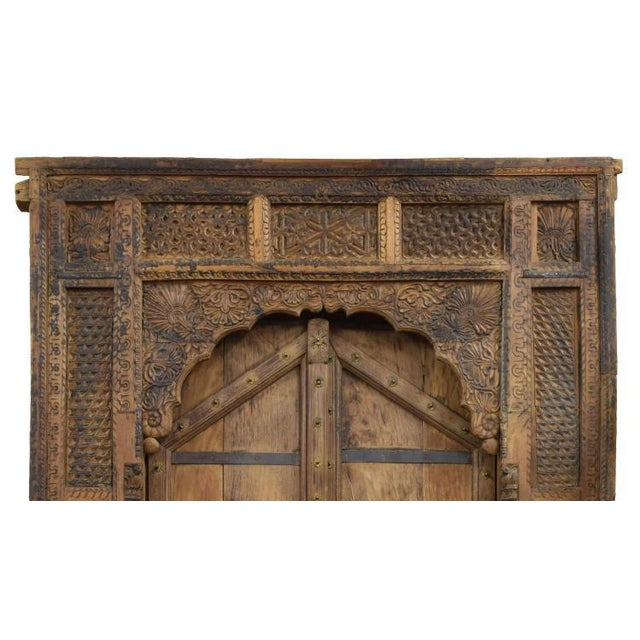 Monumental architectural teakwood door and frame, heavily carved Mughal arch frame, having floral and geometric carving...