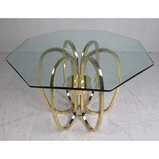 A sleek contemporary modern end table that boasts an octagonal glass top with beveled edges. The unusual brass plated base...