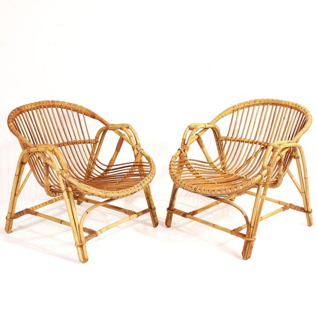 """Fabulous pair of vintage French bamboo and rattan lounge chairs from the 1960s. Stylish """"scoop"""" shape makes for..."""