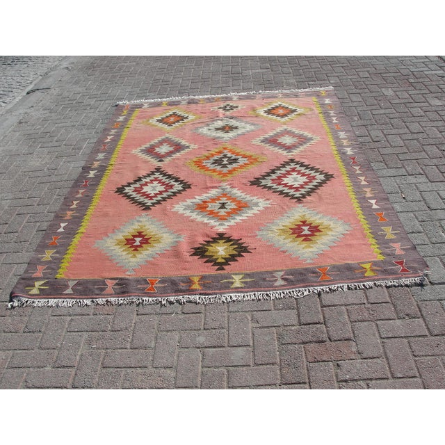 This is a vintage handwoven Turkish kilim rug. The kilim is nearly 40 years old. It is handmade of very fine quality hand...