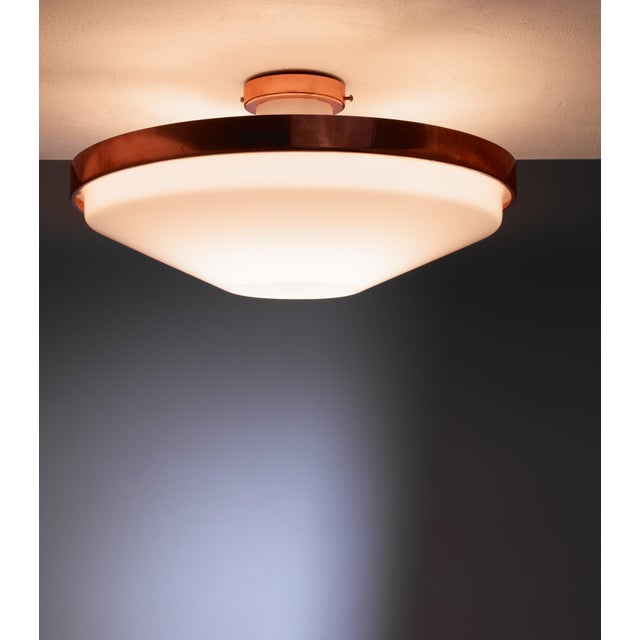 A plexiglass and copper flush mount ceiling lamp by Itsu. The lamp has an open cone shaped plexiglass diffuser in a copper...