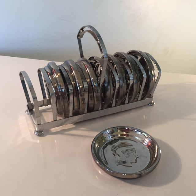 Beautiful mid-century chrome coasters/ashtrays embellished with a Roman soldier silhouette. 8 coasters with rack included....
