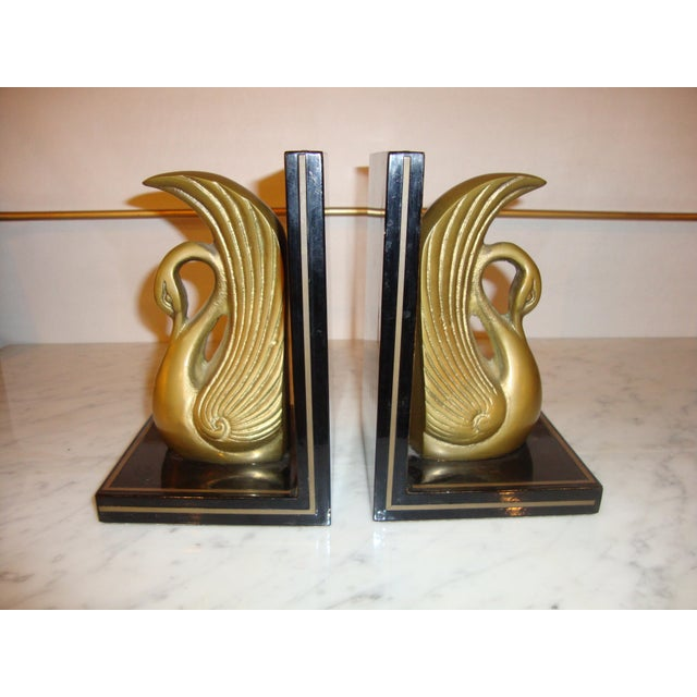This is a pair of metal Art Deco book ends, each featuring a gilt metal swan mounted on a black platform.