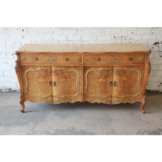 Offering a stunning Romweber burl wood French carved sideboard credenza. This piece has a stunning burl wood grain and...