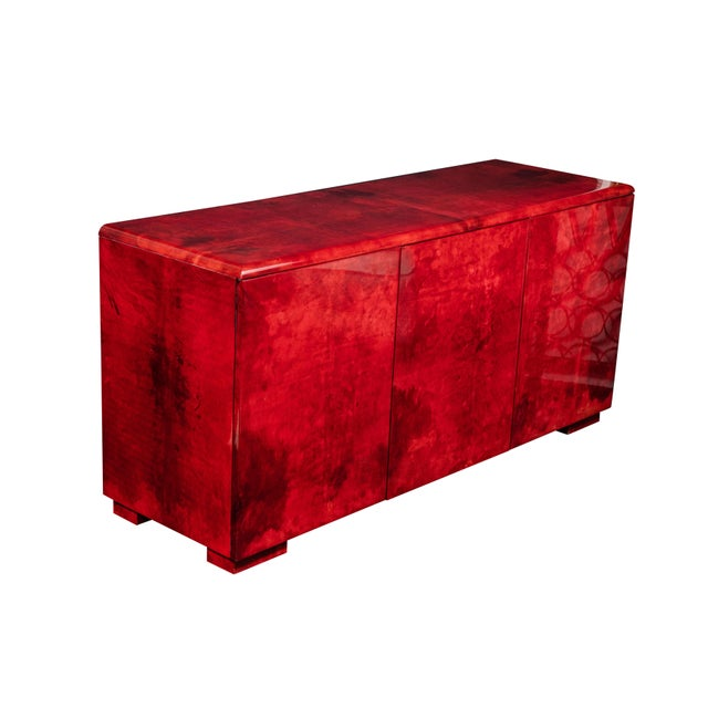 Spectacular sideboard/cabinet in rare ruby colored lacquered goatskin by Aldo Tura, circa early 1970's. The doors open to...