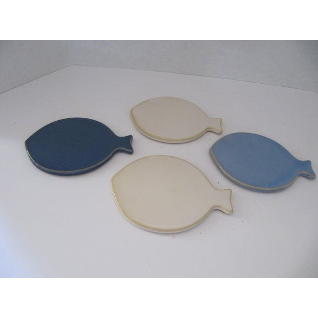 Whimisical set of 4 ceramic fish coasters with cork back. Two off white, one dark blue and one light blue.