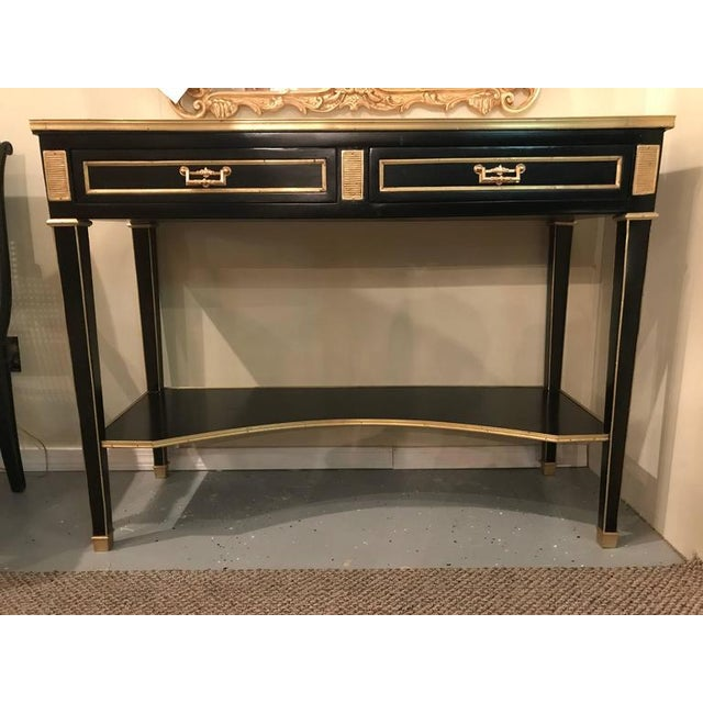 A pair of Jansen style ebonized two drawer bronze-mounted marble-top console tables. These wonderfully Russian...