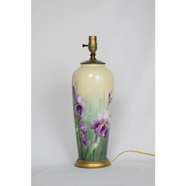 A hand painted Austrian vase. This tall Austrian made ceramic vase features hand painted purple toned iris's amidst green...