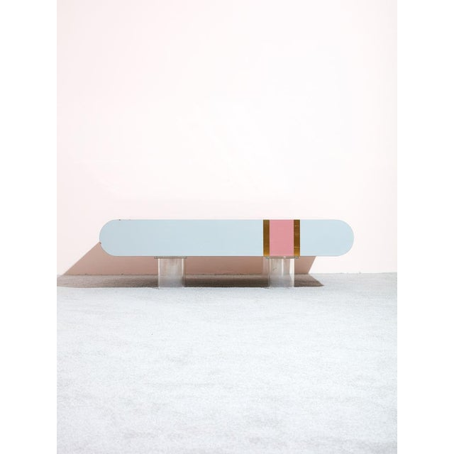 Vintage 1980s laminate coffee table with lucite legs. Features impressive gray, pink, and gold laminate striped design and...