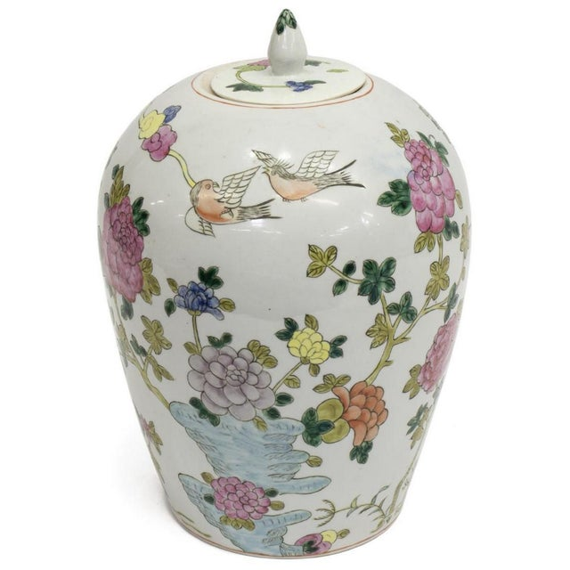 Bright and colorful, this Chinese famille rose porcelain covered jar features hand painted decoration of several birds on...