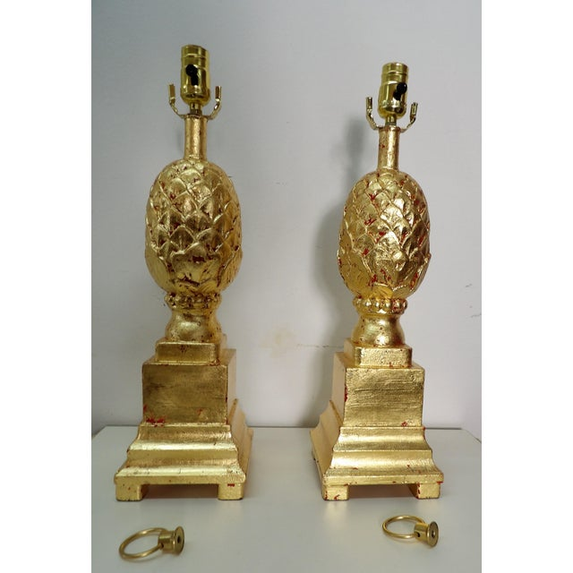 Pair of Pineapple Lamps with Gold Leaf Finish. The lamps have hints of red behind the gold leaf adding pop of color . The...