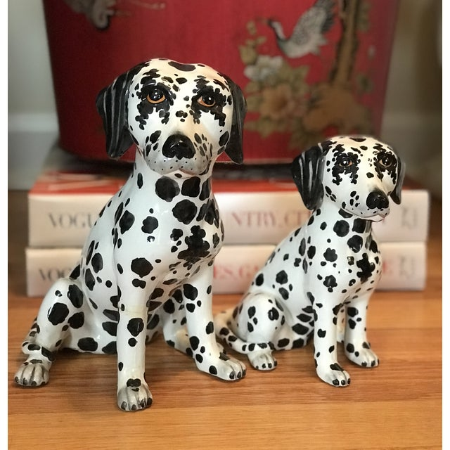 A pair of adorable hand painted ceramic spotted Dalmatian pups with expressive brown eyes. Two different sizes. Signed...