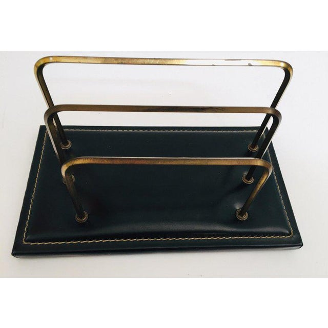 Adnet style desk set comprising of a black leather and brass letter rack, picture frame and a leather note pad with...