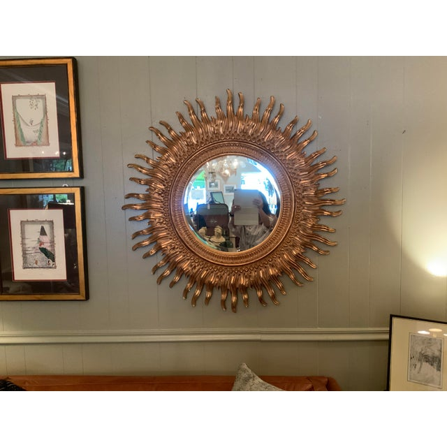 Contemporary ornate Gilded Sunburst round mirror. Slight hues of black and rose gold throughout the wood carving.