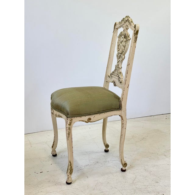 Early 20th Century Italian vanity or petite side chair finely carved in the Louis XV style. The chair is painted in cream...