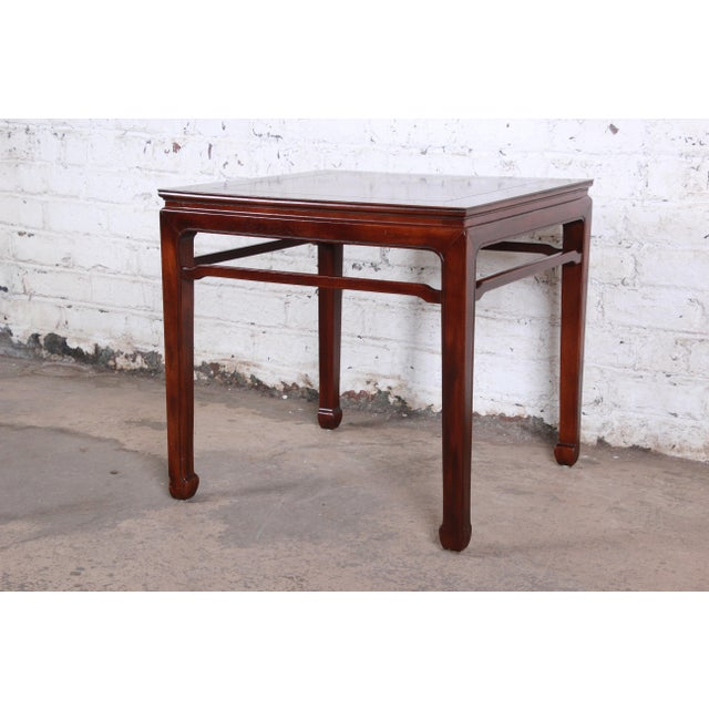 A gorgeous mid-century Hollywood Regency Chinoiserie side table by Henredon. The table features nice mahogany wood grain...