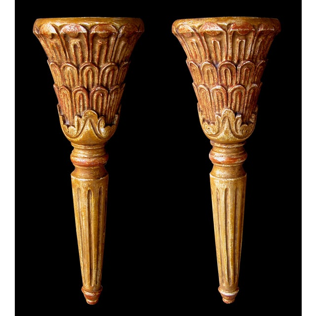 A handsome pair of Italian neoclassical style carved giltwood wall sconces; each of demilune form surmounted by a conical-...