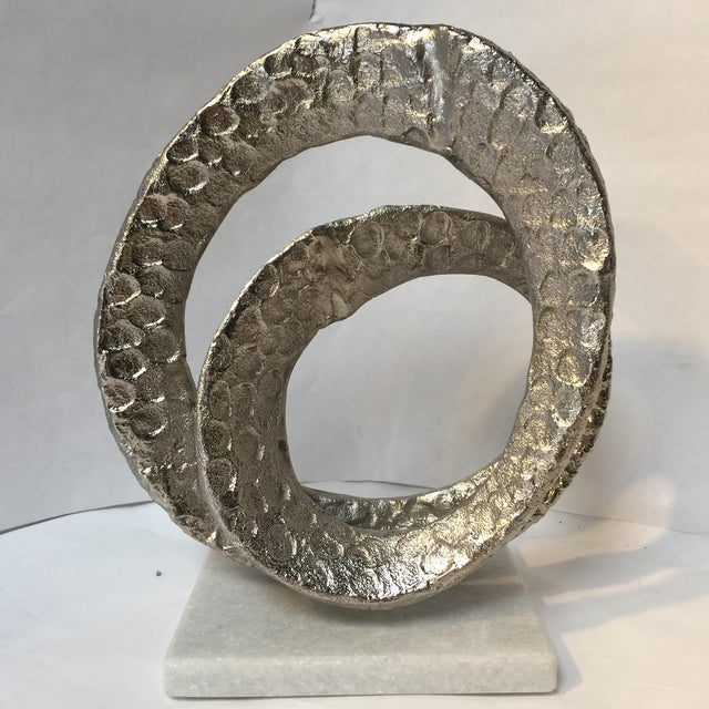 Abstract silver infinity knot on white Granite base in the Brutalist style of the mid-century. Can be bookend or desk...