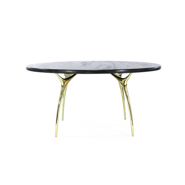 Sculptural hand casted, solid brass legs shown here in a polished finish. Solid oak top done in black ceruse highlighting...