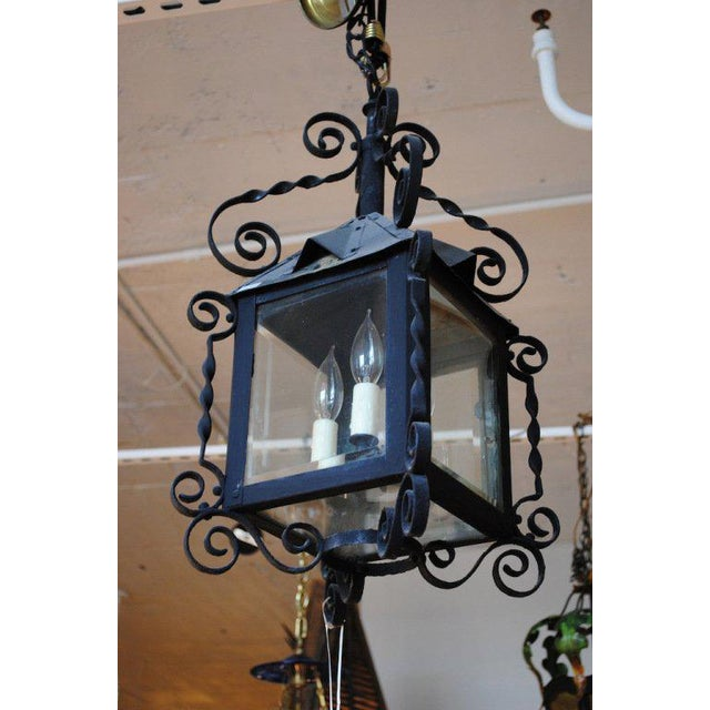 A small-scale four-sided Arts & Crafts iron lantern newly electrified with three lights and wax candle slips.