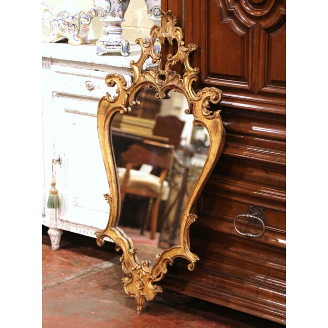 Crafted in Italy, circa 1920, the gilt mirror in the Louis XV style, features intricate carvings, including scroll and...