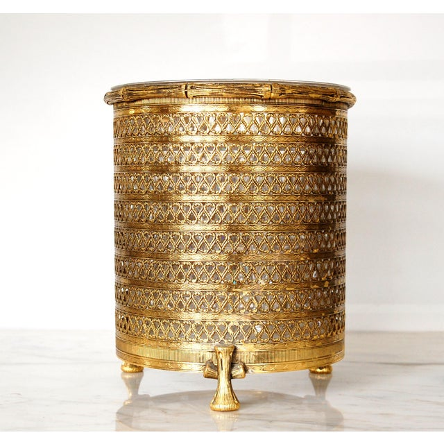 Stylish 1950's gold filigree footed waste can. Infuse a little glitz in the Powder Room! Has original acrylic liner. The...