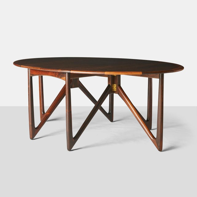 A rosewood dining table designed by Kurt Ostervig. The gatefold legs are of solid rosewood, and the table can change from...