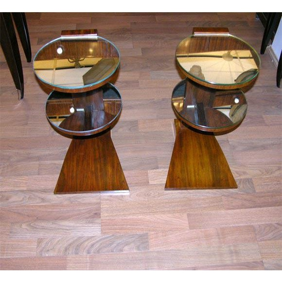 A pair of French Art Deco side tables stamped Jules Leleu, in mahogany wood and featuring two circular mirrored shelves.