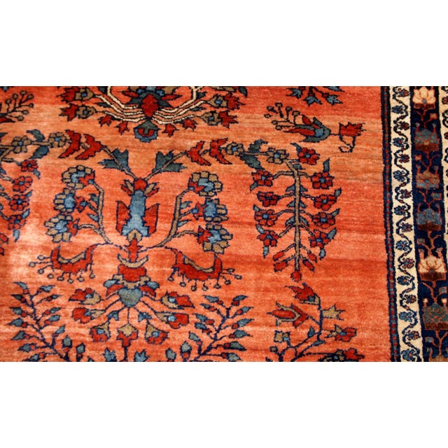 Hand made antique Persian Sarouk rug in red wool. The rug is from the beginning of 20th century in original good condition.