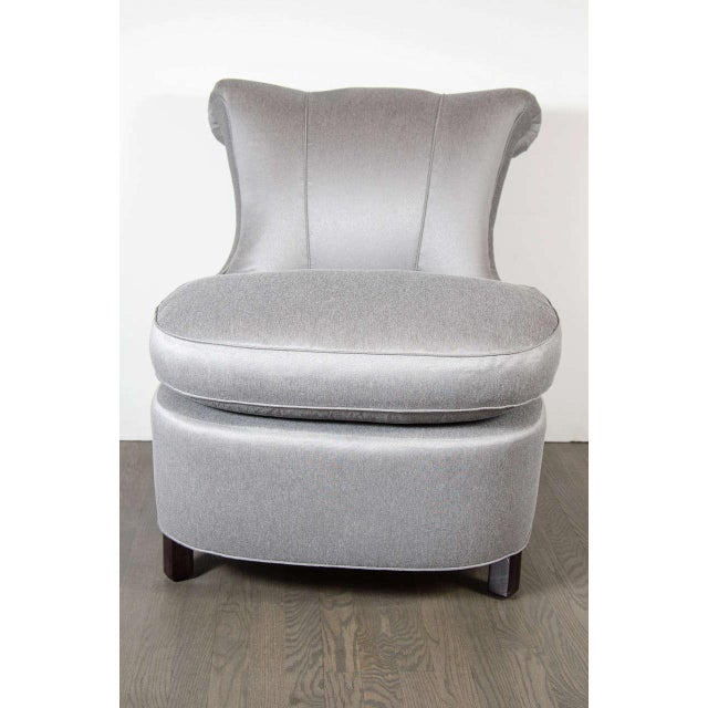 This elegant slipper chair features a scroll design and is newly upholstered in platinum sharkskin fabric with ebonized...