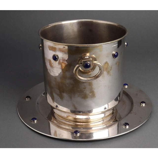 Modern silver plate ice bucket and tray with blue glass cabochon decoration and double sided handles. The plating is...