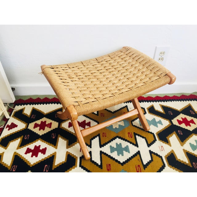 A Mid Century Hans Wegner Style folding rope stool. The seat of the stool is made of woven paper cord rope and the wood...