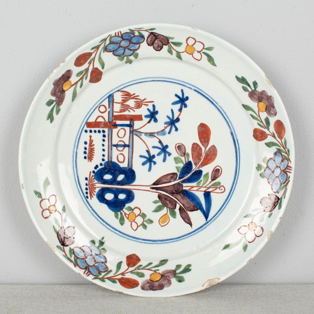 An 18th Century Delft ceramic plate, hand-painted in, blue red and green with floral decoration. Several chips to rim.