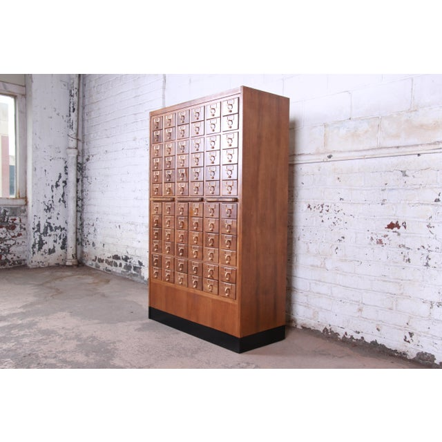 An exceptional mid-century library card catalog cabinet. The card catalog features beautiful wood grain and an amazing 72...