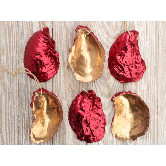 Set of six ornaments crafted from ruby red gold leafed natural oyster shells with gold lacquered cup-sides. Hand-applied...