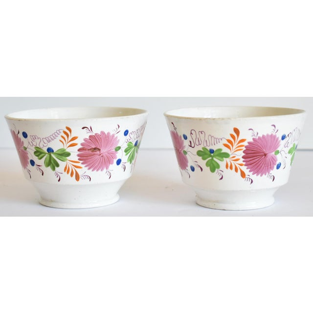 A pair of antique, early 19th-century soft paste (pearlware or creamware) Staffordshire handleless tea bowls or tea cups,...