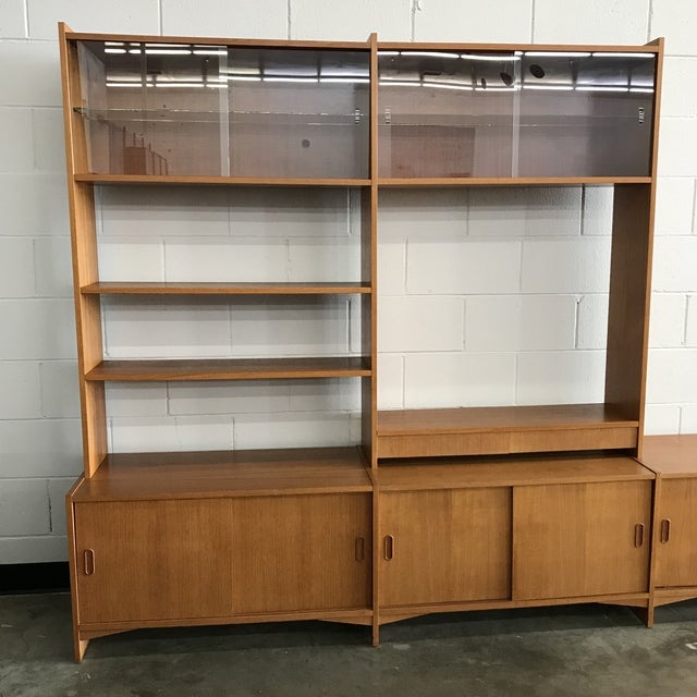 Danish modern teak freestanding wall unit. This has 3 cabinets on the bottom with sliding doors and shelves. The middle...
