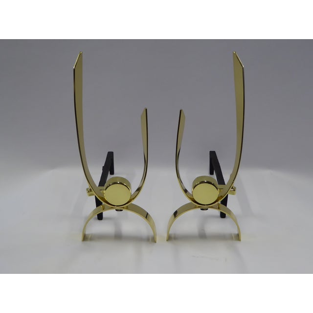 Thick polished brass ribbons arched and curved with a centered disc highlight this pair of andirons attributed to Donald...