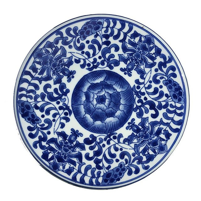 Blue and white chinoiserie ceramic floral garden stool. Top features a flat edge for sitting. Shape mimics the shape of a...