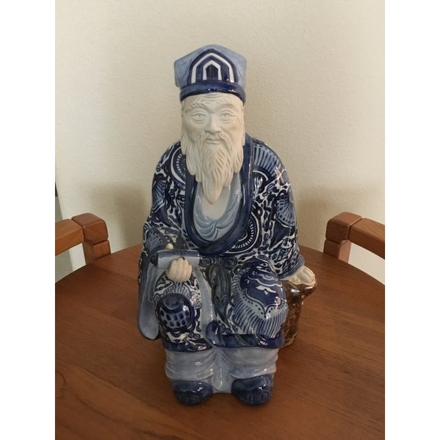 Such an interesting figure of an emperor seated with a scroll. In ceramic, in a predominantly blue and white glaze. Seated...