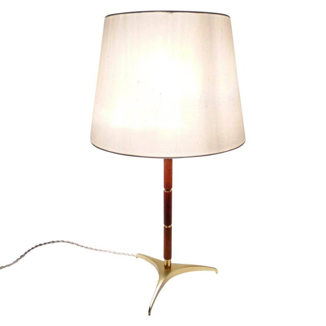 Tripod table lamp with brass feet, teak and brass bands around the base and brass finial. Newly rewired for US use. Holds...