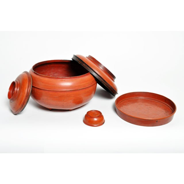 This Burmese red lacquer offering urn has different compartments for storage. Made from bamboo and lacquer, circa 1950.