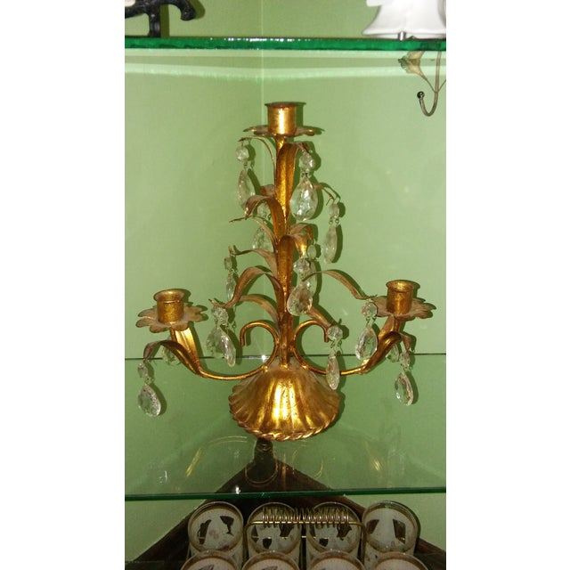 Vintage gold gilt Italian metal tole candelabra. Lead motif. Features hanging glass prisms. Holds three taper candles.