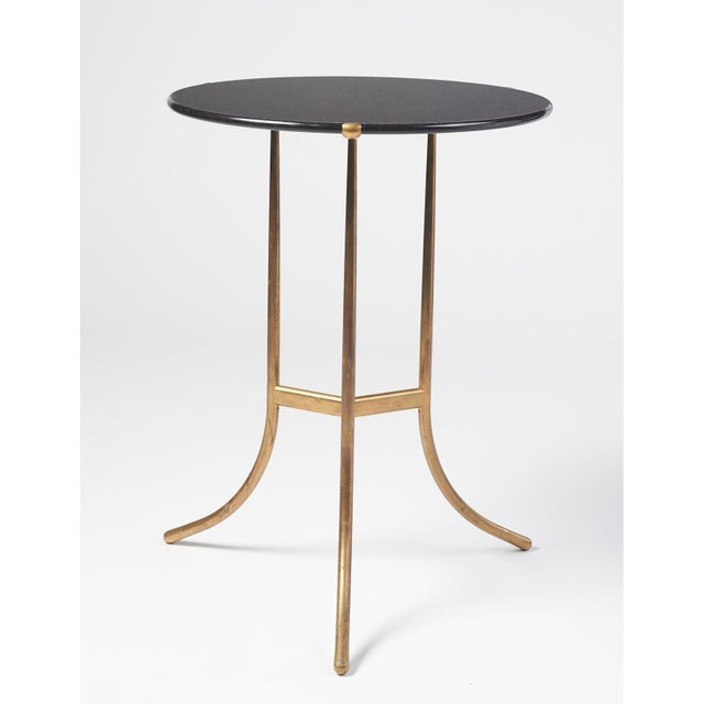 An iconic American Modern gueridon table with a polished black granite top and solid bronze rod tripod base. The granite...