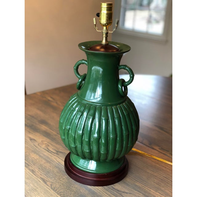 Dark green ceramic table lamp on wood base. Faux bamboo design in an urn / gourd shape with handles and rings. Solid,...