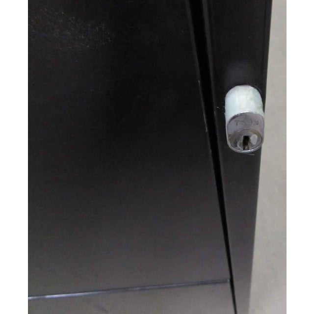 This is a large two drawer black metal file cabinet with a locking mechanism to keep your files safe and a slot to label...