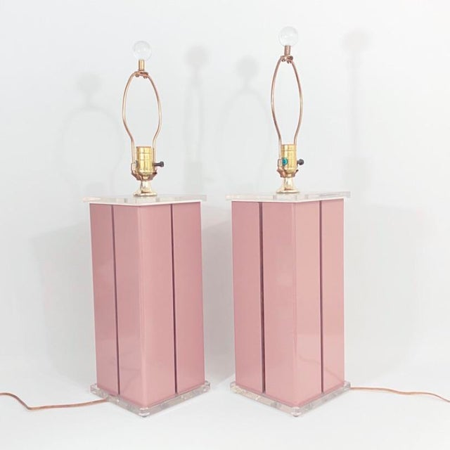 Pair of vintage lamps. Mauve base with lucite tops. Base is lacquered metal and is between two lucite pieces. The finials...